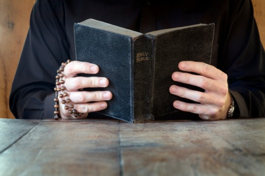Man reading antique bible, holding rosary beads on antique rustic table. With lot of copy space